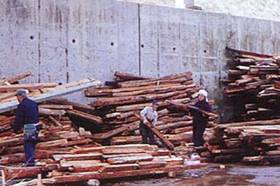 トラックで運ばれてきた産業廃棄物・木くずを仕分けます。